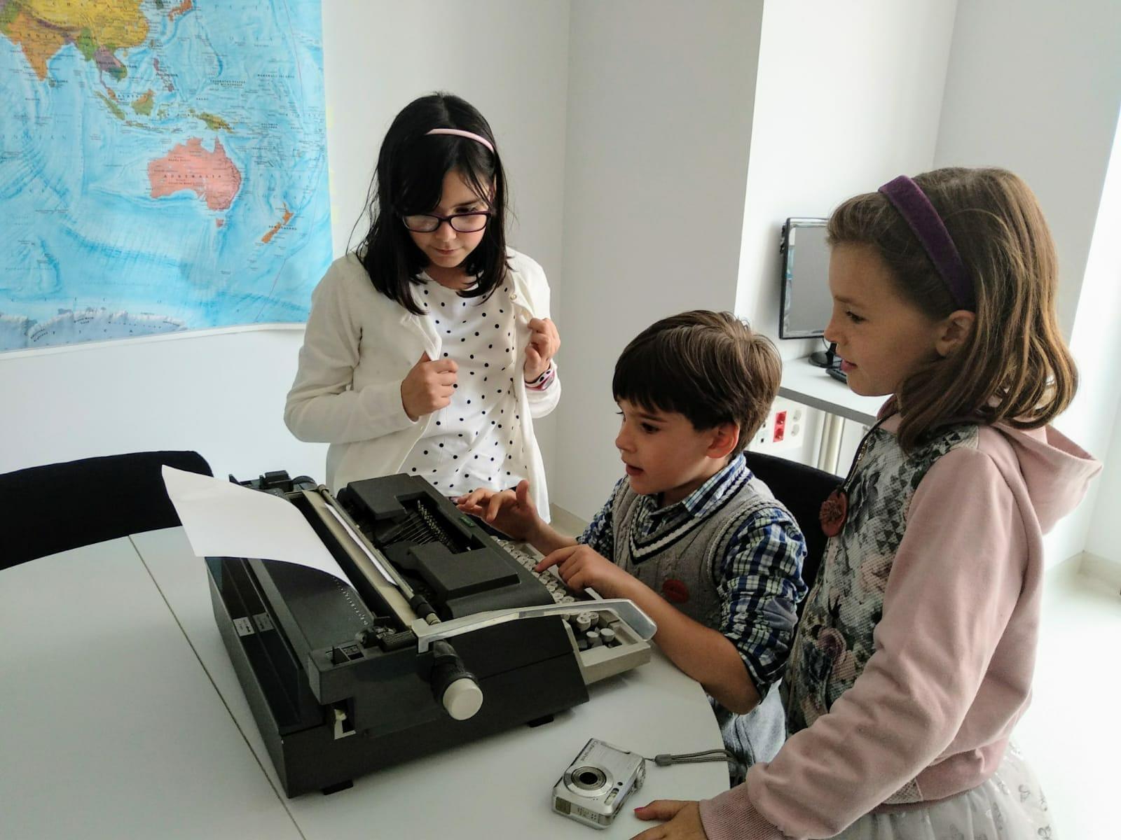 Alumnos de la escuela alternativa Mundo World con máquina de escribir
